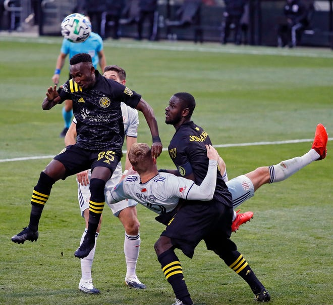 Crew defender Harrison Afful heads the ball away from New England forward Adam Buksa and runs into Columbus defender Jonathan Mensah in the Eastern Conference final at Crew Stadium on Dec. 6. The Crew won 1-0 to advance to MLS Cup.