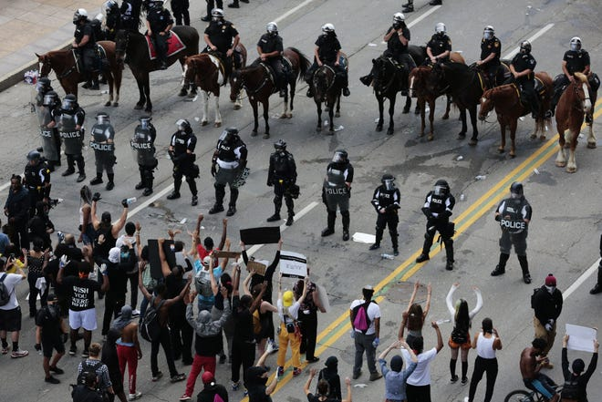 Demonstrators stand in the middle of Broad Street as Columbus Division of Police officers attempt to move them from the area during protests following the death of Minneapolis man George Floyd on Saturday, May 30, 2020 in Columbus, Ohio.