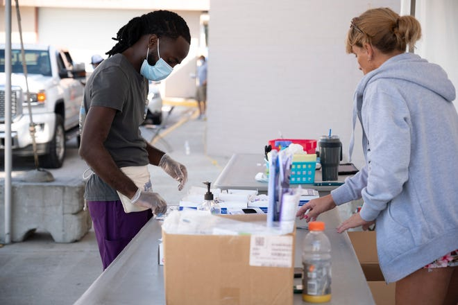 Health care workers conduct rapid tests for COVID-19 recently at the Lake Square Mall. [Cindy Peterson/Correspondent]
