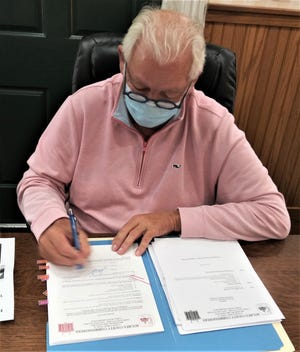 Holmes County Commissioner Joe Miller signs a document at a recent commissioners meeting. The commissioners on Monday gave the OK for the county to move ahead with a survey by the Ohio Department of Transportation about the recommended reduction of speed limit on County Road 172.