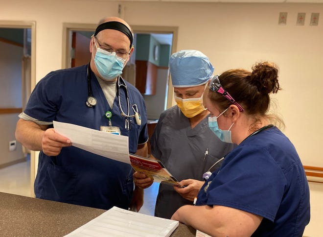 Staff members at Wooster Community Hospital review notes. The hospital and all of its services continue to operate without disruptions due to COVID-19.