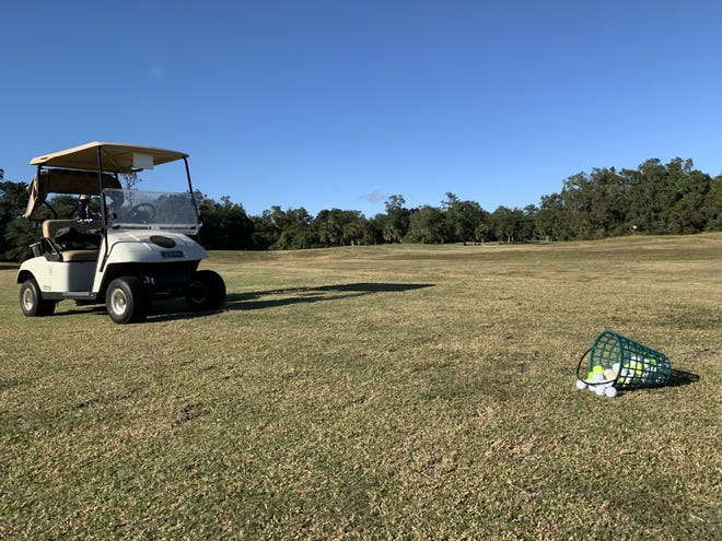 A golf cart and a bucket of golf balls can be seen at River Bend Golf Club in Ormond Beach on Monday, Dec. 7, 2020.