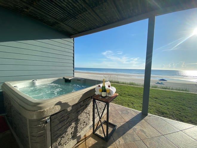The private walk-out oceanfront deck has a hot tub for relaxing while enjoying the views.