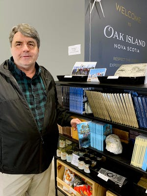 """James McQuiston, of North East, shows off some of his books that are for sale at the Oak Island Interpretive Center in Nova Scotia, Canada. He has worked for four years with the people involved in the hunt for treasure there and has made 10 trips to the island featured on the TV show """"The Curse of Oak Island."""""""