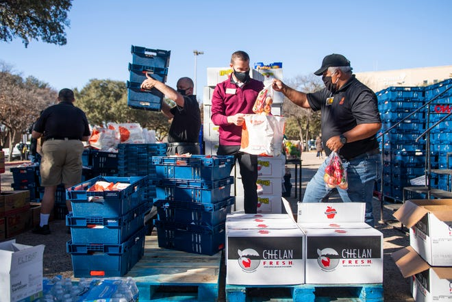 United employees unload a truck to hand out gift bags to Covenant Hospital workers at Covenant Children's Hospital Monday, Dec. 7, 2020, in Lubbock, Texas.