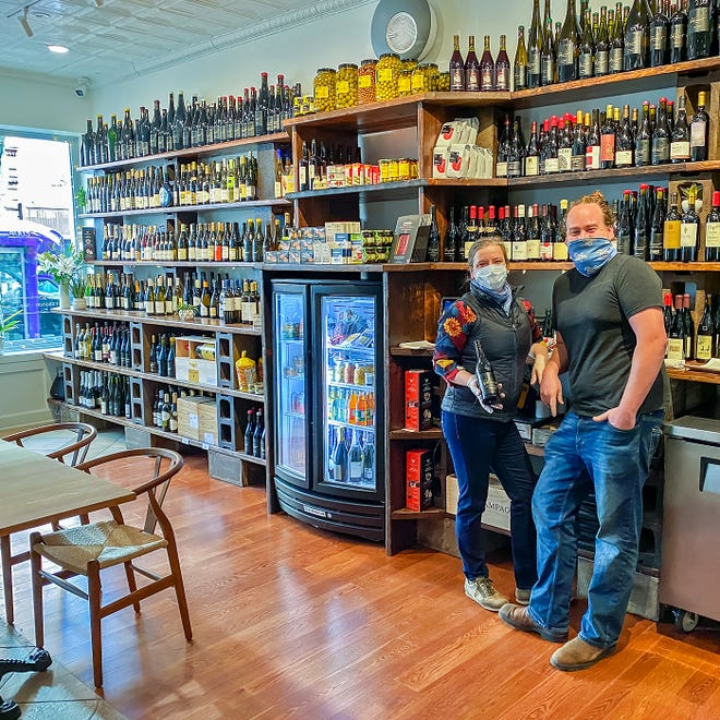Christopher Bates and Isabel Bogadtke, owners of F.L.X. Provisions, stand in front of the many items sold at the 2-4 E. Market St. business. Two additional attractions, a bistro and a steakhouse, are expected to fill the rest of the building by the end of the year.