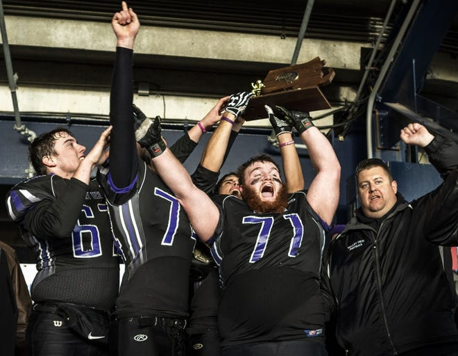 Former Blackstone Valley football player Ethan Blake holds up the trophy as the captains celebrate defeating St. Mary's for the Div. 7 state championship at Gillette Stadium on Dec. 1, 2018.
