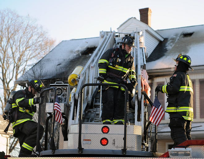 Firefighters talk from atop the ladder truck after bringing a two-alarm fire under control at 31 Felton St. in Hudson, Dec.  7, 2020.