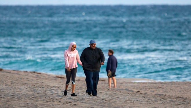 People dressed for the cold temperatures for their morning walk on Midtown Beach in Palm Beach on Dec. 1, 2020. It was 55 degrees with a 16 mph wind at sunrise.
