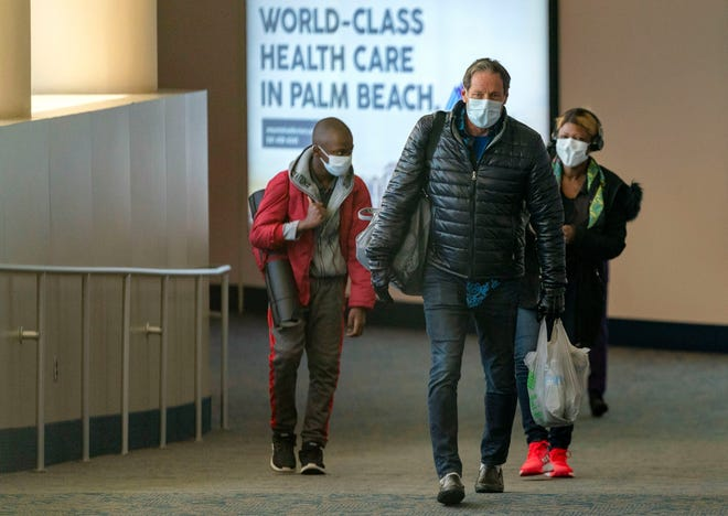 Passengers arrive from Newark, N.J. to Palm Beach International Airport in West Palm Beach, Florida on March 24, 2020.