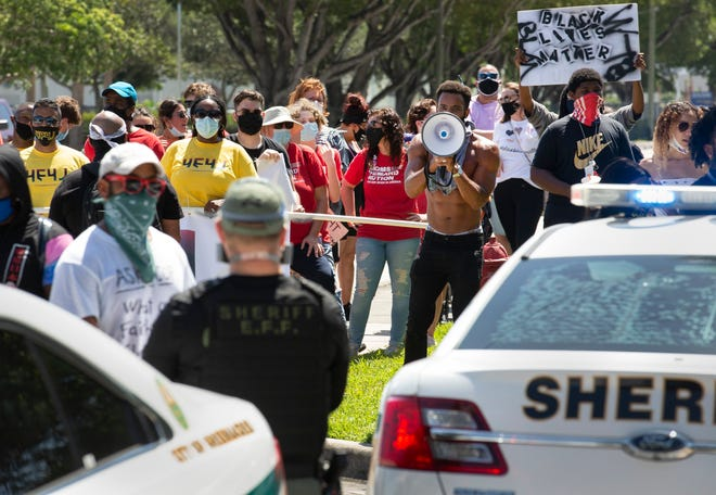 "Protesters at a ""March 4 Justice"" rally gather outside the Palm Beach County Sheriff's Office in suburban West Palm Beach on July 25, 2020."