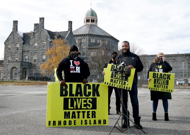 Mark Fisher, senior director of Black Lives Matter Rhode Island, speaks outside the ACI maximum-security facility Monday morning. At left is the organization's executive director, Brother Gary Dantzler.