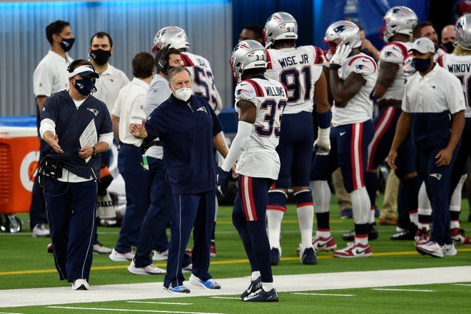 Patriots head coach Bill Belichick shakes hands with Joejuan Williams during the second half of Sunday's  game against the Los Angeles Chargers. New England cruised to a 45-0 victory and now sits at 6-6 this season.