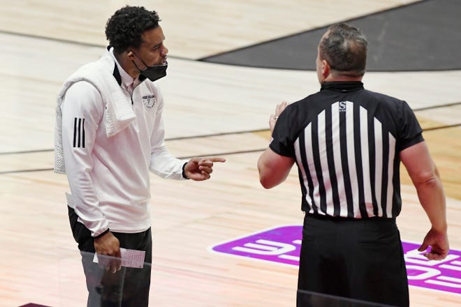 URI head coach David Cox, left, talks with an official during a Nov. 28 game against South Florida. URI scheduled a last-minute game with No. 13 Wisconsin for Wednesday.