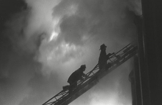 Providence firefighters work to extinguish the blaze on the fourth floor of Providence College's Aquinas Hall dorm in the early morning hours of Dec. 13, 1977.  Ten women died in the fire.