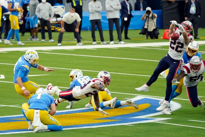New England Patriots defensive back Cody Davis (22) blocks a field goal attempt from Los Angeles Chargers kicker Mike Badgley, left, during the first half of an NFL football game, Sunday, Dec. 6, 2020, in Inglewood, Calif. The ball was recovered by New England's Devin McCourty, bottom center, who returned the ball for a touchdown. (AP Photo/Ashley Landis) ORG XMIT: CAMS114