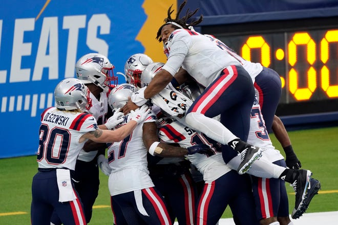 The New England Patriots celebrate after Devin McCourty returned a block field goal attempt for a touchdown during the first half of an NFL football game against the Los Angeles Chargers Sunday, Dec. 6, 2020, in Inglewood, Calif.