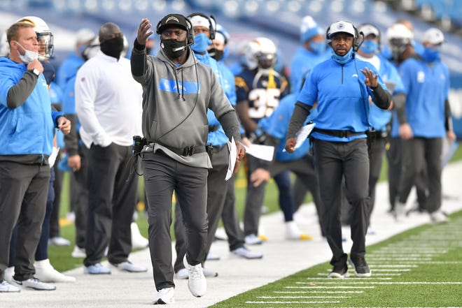 Los Angeles Chargers head coach Anthony Lynn, left, works the sideline during the second half of an NFL football game against the Buffalo Bills, Sunday, Nov. 29, 2020, in Orchard Park, N.Y. (AP Photo/Adrian Kraus)