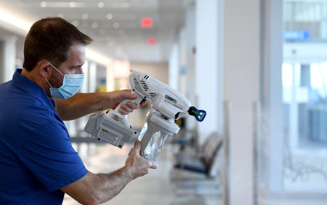 Rodney Doane with Akron-Canton Airport sprays a special disinfecting solution, one measure which has helped them receive global health accreditation from the Airports Council International. Friday, Dec. 4, 2020.