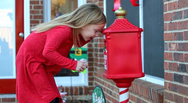 Olivia Jolly, 5, checks to make sure her letter to Santa entered the mailbox located outside Jolly Realty Group on Tuesday.