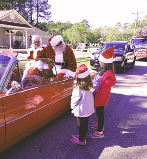 Sisters McKenna and Delaney Anderson tell Santa what they'd like for Christmas during A Very Merry Little Car Parade on Dec. 5 in Richmond Hill.