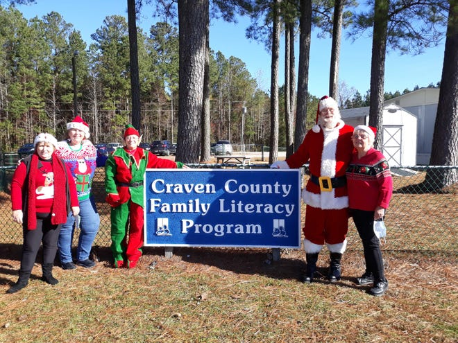 """For the past 12 years, the New Bern Civitan Club has sponsored a Santa Land at its tree lot inviting over 200 children in the Craven County Pre- School and Family Literacy Program to meet and have their pictures taken with Santa as well as receiving gifts donated by Club and Community members.  This year because of the pandemic, no field trips outside the school were permitted for safety reasons.  Instead, Santa and his elves have taken some road trips.  They have visited the schools that house children enrolled in the program. One of their visits was to the Vanceboro Family Literacy and Pre-K program. Pictured from left, Elves Judy Lopez, Eileen Buscemi, Mary Traina, Santa Jim Comer and """"Mrs. Claus"""" Maureen Comer. [CONTRIBUTED PHOTO]"""
