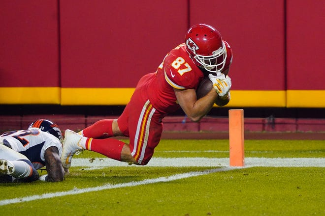 Chiefs tight end Travis Kelce scores a touchdown beyond Broncos strong safety Kareem Jackson during the second half Sunday night at Arrowhead Stadium.