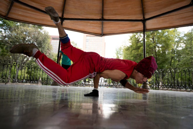Carlos Cruz, a breakdancer, practices at a kiosk in Alameda park after being closed off to the public for nearly five months due to the new coronavirus pandemic in Mexico City. Breakdancing has been confirmed as an official Olympic sport.