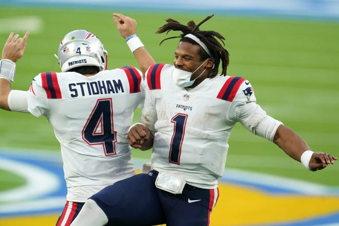 Patriots quarterbacks Cam Newton (1) and quarterback Jarrett Stidham (4) celebrate after a fourth-quarter touchdown.