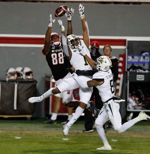N.C. State wide receiver Devin Carter (88) makes the reception as Georgia Tech defensive back Juanyeh Thomas (1) defends during the first half of N.C. State's game against Georgia Tech at Carter-Finley Stadium in Raleigh, N.C., Saturday, Dec. 5, 2020.