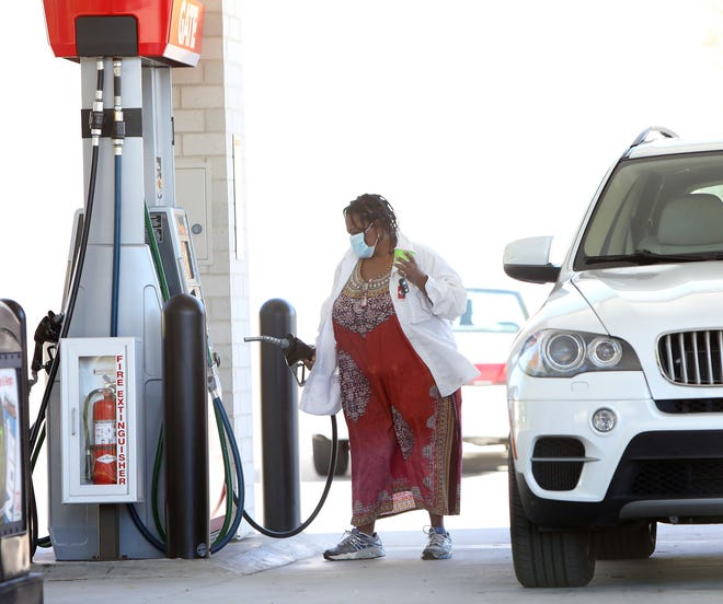 A woman pumps gas at the Gate Gas Station off 13th Street on Monday in Gainesville. [Brad McClenny/The Gainesville Sun]