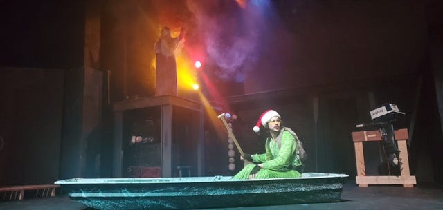 """Dalton Cotter portrays Meshack Lutterloh in his jon boat as part of """"A Cedar Key Christmas,"""" now onstage at the Gainesville Community Playhouse. (Photo courtesy of Gainesville Community Playhouse)"""