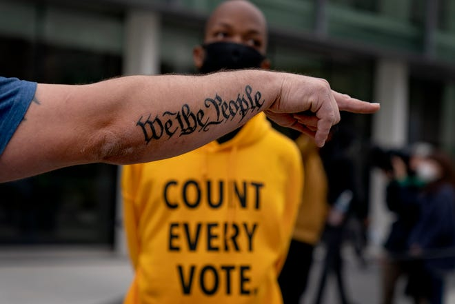 """In this Nov. 5 photo, the tattoo """"We The People"""" decorates the arm of a Trump supporter as he argues a counter protestor while Trump supporters demonstrate against the election results outside the central counting board at the TCF Center in Detroit."""
