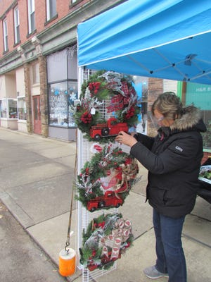 Chris McMullen of B&C Creations adjusts a wreath at the booth on Main Street during Christmas Reimagined Saturday afternoon in Newcomerstown.