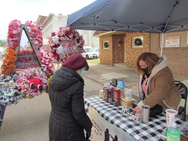 Tiffany Camburn (right) of & Then There's You 2 Craft's and Such, shows some of the items for sale during Christmas Reimagined on Main Street in Newomerstown Saturday.