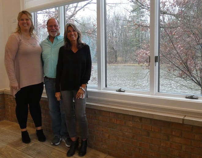 Manager Cameo Carey stands with owners Bill and Polly Chandler in the main dining room at the Water's Edge Event Center, which will be reopening soon.