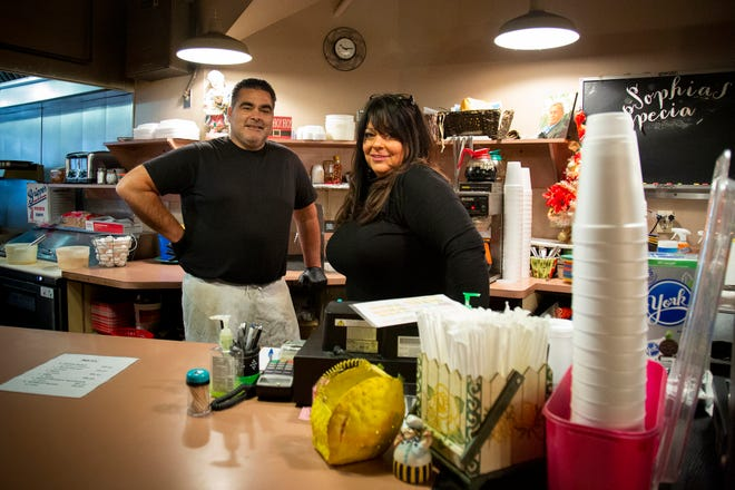 Brother and sister duo Pete and Diane Georges poses behind the counter at Sophia's Deli & Restaurant in downtown Cincinnati on Monday, Dec. 7, 2020. Sophia's has been a downtown lunch staple for more than 26 years but has suffered in 2020 as their regular lunch crowd has worked from home.