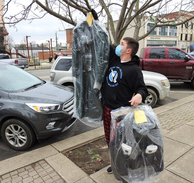 Bailee Cass, a student at the Coshocton Opportunity School, hangs coats on Main Street for the needy and homeless part of a winter clothing drive. The project is similar to one in Europe where coats were placed on trees for those who need to them to come and take.