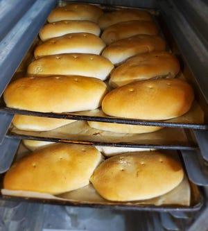 Roti pizza yang baru keluar dari oven di rak di Villa Bakery di Garden City.