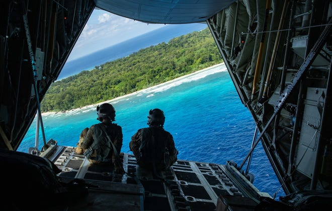Staff Sgt. Hector Frietze, right, and Senior Airman John Allum, left, 36th Airlift Squadron loadmasters, prepare for the first bundle airdrops of Operation Christmas Drop 2020, at the Island of Angaur, Republic of Palau, on Dec. 6. In addition to the U.S. Air Force, the Japan Air-Self Defense Force also participated in the effort