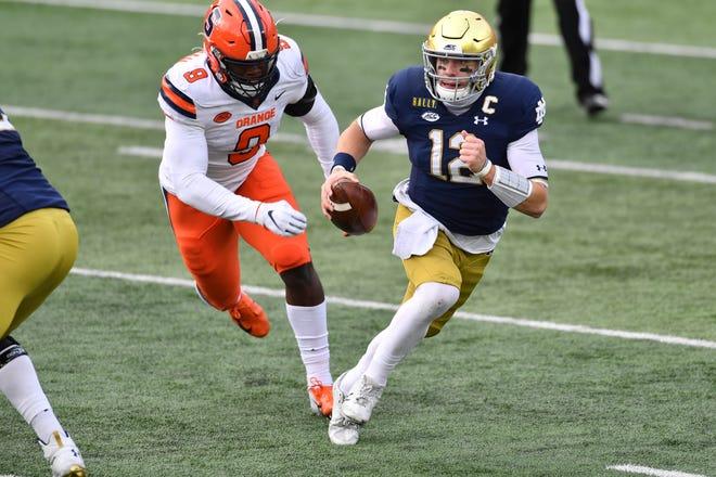 Notre Dame Fighting Irish quarterback Ian Book (12) runs as Syracuse Orange wide receiver Sharod Johnson (8) pursues in the second quarter at Notre Dame Stadium.