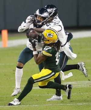 Green Bay Packers wide receiver Davante Adams (17) pulls down a long reception against Philadelphia Eagles cornerback Avonte Maddox (29) and cornerback Darius Slay (24) in the third quarter during their football game Sunday, December 6, 2020, at Lambeau Field in Green Bay, Wis.