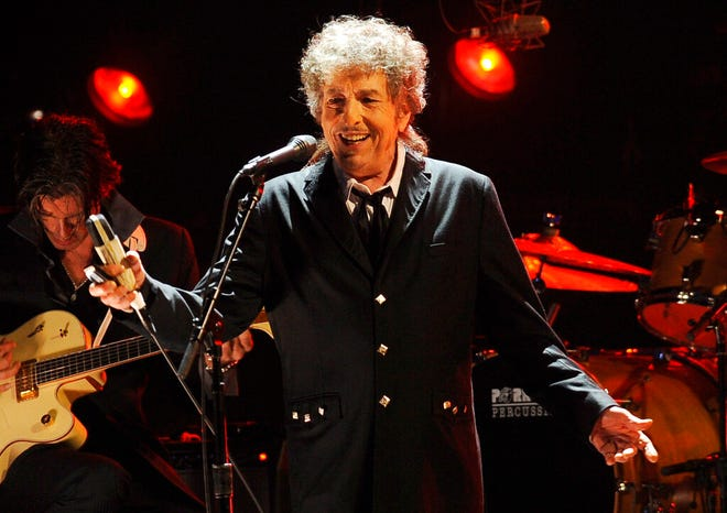 """FILE - Musician Bob Dylan performs in Los Angeles on Jan. 12, 2012. Transcripts of lost 1971 Dylan interviews with the late American blues artist Tony Glover and letters the two exchanged reveal that Dylan changed his name from Robert Zimmerman because he worried about anti-Semitism, and that he wrote """"Lay Lady Lay"""" for actress Barbra Streisand. The items are among a trove of Dylan archives being auctioned in November 2020 by Boston-based R.R. Auction. (AP Photo/Chris Pizzello, File)"""