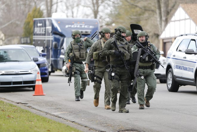 SWAT team members walk Monday afternoon along South B Street after being activated for a call on South 48th Street.