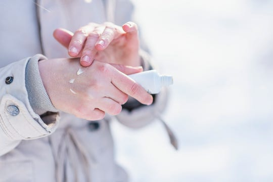 A woman applies moisturizer cream to hydrate her hands.