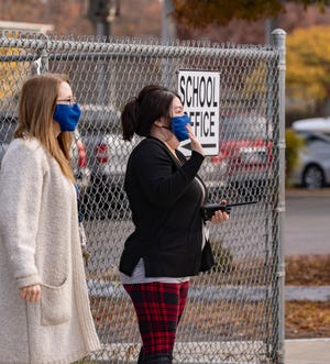 Pinkham teachers wave to Pinkham Elementary School students returning to classrooms Monday, December 7, 2020. Visalia Unified School District leaders have said they are adhering to federal health protocols.
