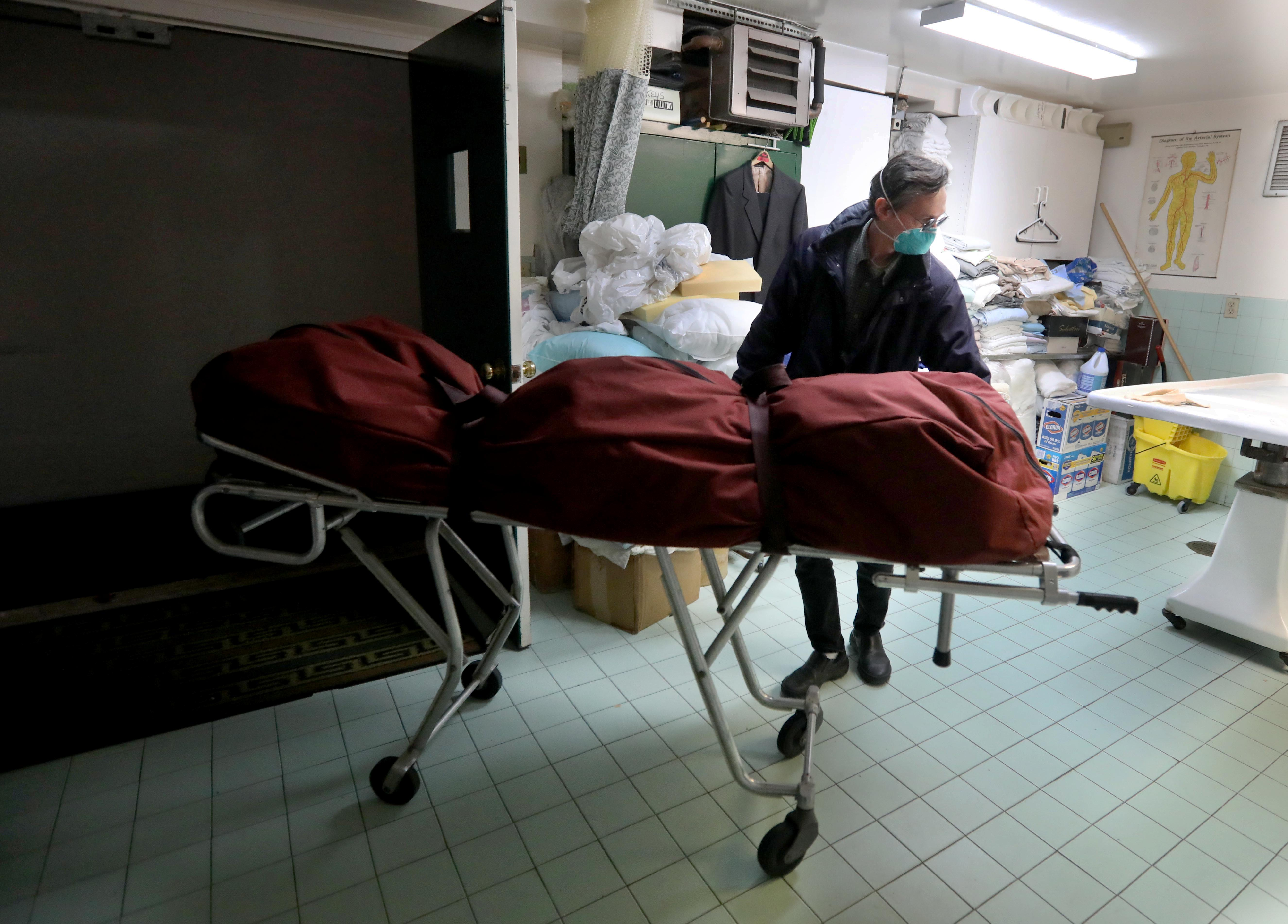 At the start of the COVID-19 pandemic, funeral directors went from handling four funerals a week to at least five burials or cremations daily. Here funeral director Mark Flower places a body that he just picked up from the New York City Medical Examiner's office in the prep room of his Yonkers funeral home.