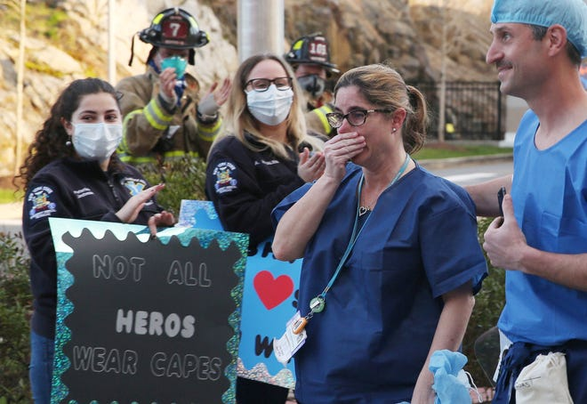 A nurse cries before starting her night shift at Northern Westchester Hospital in Mount Kisco, New York, last April. First responders from across the area gathered to applaud nurses getting off work and starting work at the hospital.