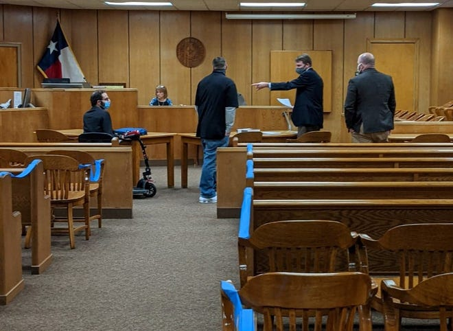Wichita County Assistant District Attorney Kyle Lessor, fourth from left, responds when murder defendant Justin Michael Love, third from left, approaches him after a hearing Monday, Dec. 7, 2020, in 30th District Court.