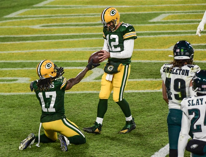 Green Bay Packers wide receiver Davante Adams (17) hands the ball to quarterback Aaron Rodgers (12) after scoring a touchdown in the third quarter against the Philadelphia Eagles at Lambeau Field.
